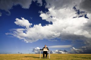man working at desk under clouds