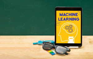 Machine learning bot on tablet with glasses on wood table and green blackboard with copy space for adding text.Artificial intelligence learning concept.