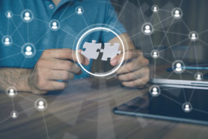 supplemental IT support and outsourcing concept illustration with man holding puzzle pieces together.