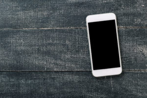 photo of smartphone on gray wooden table.