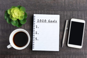 photo of notebook with 2020 goals list written in it on a table with a cup of coffee, smartphone and plant.