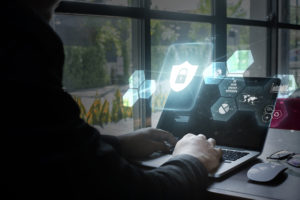 person typing on laptop with floating and glowing shield and lock icon in front of the screen, illustrating security.