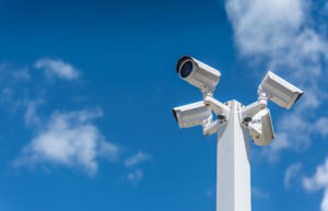 Four white security cameras in front of a blue sky with clouds.