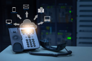 """Office phone on a desk with email, laptop and other tech symbols surrounding it with arrows pointing to them, and text that says """"Cloud PBX"""" to represent a cloud phone system."""
