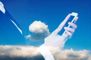 A woman in a black suit jacket and white shirt underneath holds a smartphone against a backdrop of blue sky and clouds to symbolize cloud contact center capabilities.