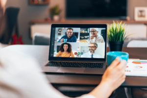 Woman on laptop videoconferencing with four colleagues and other remote workers on screen.