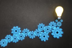 Blue gears ascending from left to right against a black background with a glowing light bulb on the right, to illustrate digital transformation.