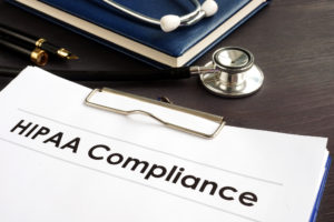 Clipboard with a piece of paper that says HIPAA compliance next to a stethoscope on a desk.