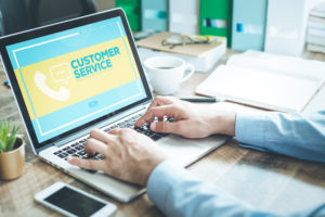 """Laptop on a desk with the screen showing the words """"Customer Service"""" and a phone icon against a yellow background."""