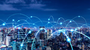 City skyline at night with glowing connected dots over it to represent networking.