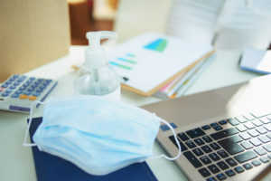 A medical facemask and container of hand sanitizer on a desk near a laptop to represent IT strategy considerations post-COVID-19.