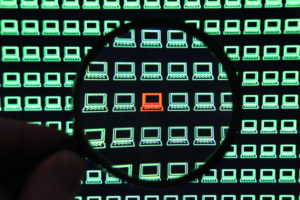 A close up view of a person holding a magnifying glass over a screen covered in rows of tiny glowing green computers. One computer glows red, at the center of the magnifying glass, symbolizing a machine infected with malware.