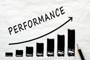 A black bar graph on white paper with the bars growing in size, with an arrow drawn above the bars illustration the upward trend and the word PERFORMANCE written along the top curve of the arrow. A black pencil sits beside the graph on the right side.