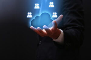 A person reaches out from a dark background with their hand palm up and holding a glowing blue cloud with four pairs of icons symbolizing people hovering around its edges.