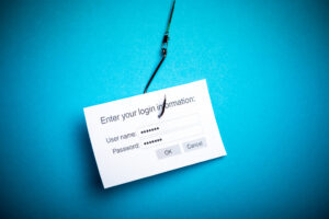 A login widget asking for username and password dangles on a fishing hook in front of a blue background, symbolizing a phishing scam.