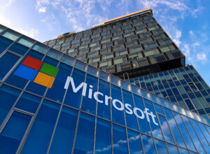 An office building angled from below, showing a blue sky and the Microsoft name and logo in the foreground.