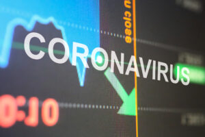 A screen shows the word CORONAVIRUS with an arrow with a downward trajectory, symbolizing the economic downturn caused by the pandemic.