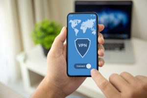 """Close up of a remote worker's hands holding a smartphone that shows a map of the world and a shield icon that says """"VPN"""" on it, switching the app on."""