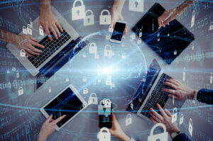 A group of people seen from above work on laptops and tablets with floating padlocks superimposed over the image, symbolizing zero-trust network security.