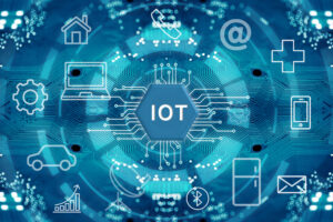 The letters IOT, standing for Internet of Things, sit at the center of a circle of symbols for devices like homes, laptops, a fridge and so on.