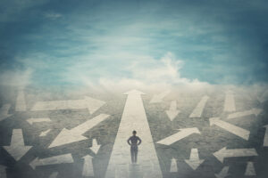 A silhouette of a person in the foreground faces an arrow-shaped path pointing straight toward the horizon and a blue sky filled with faint clouds, while numerous other arrows point in different directions on either side of the figure in the foreground.