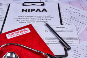 A stethoscope lies on top of a pile of papers, including a clipboard with a paper that says HIPAA on it in large letters.