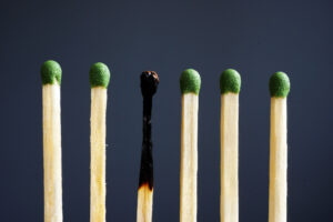 Six matches with green heads stand against a dark gray background, with the third one burned, to represent the concept of burnout.