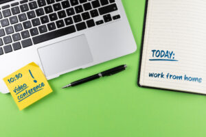"A laptop keyboard and notepad sit against a lime green background, with a note that says ""TODAY work from home"" on the notepad and a reminder for a 10:30 videoconference on a post-it note on the laptop."