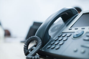 Close up of a black office phone on a desk.