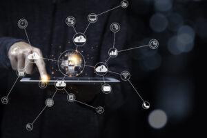 A man in dark clothing holds and points to the surface of a tablet, which has symbols representing the cloud, AI and other technologies in a connected web superimposed over it.