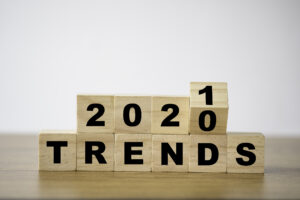 Wooden blocks spell out 2020 TRENDS in black numbers and letters, with the last block with 0 on it rotating to show another side with a 1 on it to change it to 2021 TRENDS.