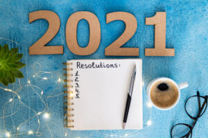 """Large numbers spell out 2021 above a notebook with """"Resolutions"""" written in it, a cup of coffee and a pair of glasses, to illustrate setting IT resolutions."""