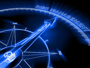 A close up of part of a glowing blue compass against a black background. The needle is point to the words RISK MANAGEMENT to symbolize cybersecurity risk management.