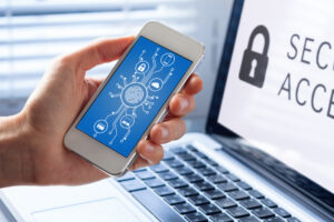 A person holds a smartphone displaying security-related symbols while working on a laptop. The laptop screen shows a padlock symbol and the words SECURE ACCESS to symbolize secure remote work.