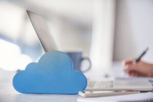 A woman works on a laptop in the background with a blue cloud icon in the foreground, symbolizing cloud computing.