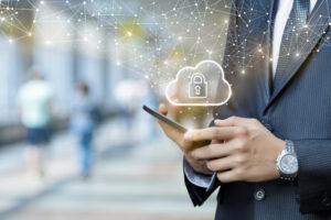 A businessman holds a smartphone with a cloud icon containing a padlock symbol floating over it, symbolizing a cloud-delivered secure access service edge.