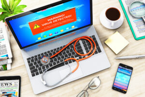 """A laptop with a red stethoscope on the keyboard displays a bright red warning message reading """"WARNING: VIRUS DETECTED."""""""