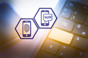 Two icons representing smartphones showing a fingerprint scan and security code made up of a sequence of numbers are superimposed over a laptop keyboard, representing multi-factor authentication.