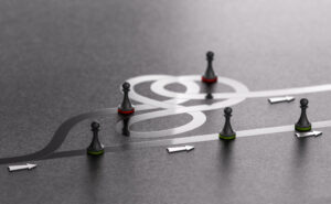 Game pieces follow arrows and looping paths on a gray surface, symbolizing the infinite game of business.