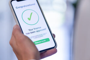 """A woman holds a smartphone displaying a green check mark on the screen and the message """"Congratulations! Your finance has been approved,"""" implying she has been approved for a loan via a mobile banking app."""
