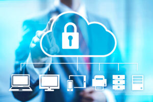 A man in a suit in the background points to the outline of a cloud with an unlocked padlock inside it and smaller icons representing devices like a laptop linked to it below.