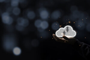 Against a blurry dark bluish background, a person holds a glowing image of a cloud with up and down arrows inside it in the palm of their hand, symbolizing cloud computing.