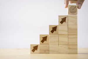 A pyramid of wooden blocks with arrows pointed on them progressing upward, with a hand placing a block with a target printed on it at the top.