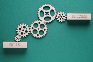 """Two wooden rectangular blocks (one on the lower left that says """"skills"""" and another on the upper right that says """"success"""") are connected by five wooden gears of various sizes."""