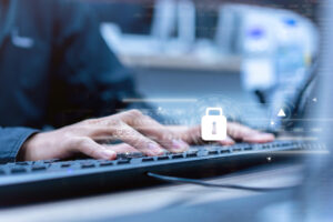A close up photo of a person's hands on a keyboard with a white padlock icon floating over the keyboard, symbolizing endpoint security.