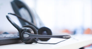 A headset sits on a desk with an out-of-focus desk phone in the background, symbolizing a call center.