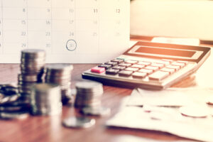 Piles of coins rest next to a calculator in front of a calendar with the 31st circled to represent expense management.