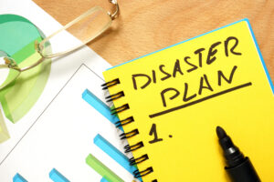 A yellow notebook lies on top of other papers on a desk with the words DISASTER PLAN and the start of a numbered list.