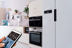 """A person holds a smartphone that says """"IoT"""" on it for Internet of Things in a kitchen, with lines and dots representing connections between the smart kitchen devices and the smartphone."""