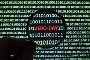 """A hand holds a magnifying glass up to a screen filled with green ones and zeros to enlarge red text that says """"ZERO-DAY,"""" representing zero-day malware."""